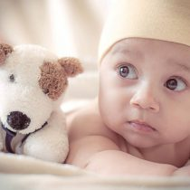 Brown eyes baby with yellow hat and toy dog – Birth, Baby & You – Dee Bell – Lactation Consultant for Kent, Surrey & Sussex